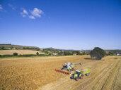 Aerial view combine harvester filling tractor trailer in sunny rural barley field - JUIF01224