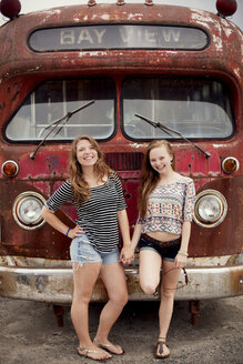 Smiling girls holding hands near dilapidated bus - BLEF05864