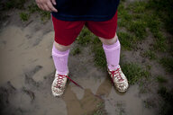 Girl wearing sneakers in mud puddle - BLEF06068