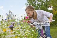 Girl on bicycle smelling wildflower in field - JUIF01243