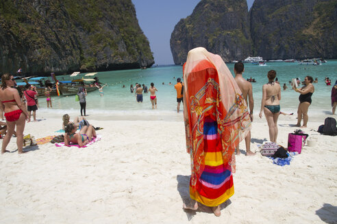 Woman in traditional headscarf standing on beach - BLEF06099