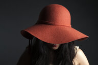 Asian woman hiding behind red hat - BLEF06132