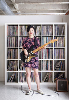 Taiwanese woman playing electric guitar near record collection - BLEF06138