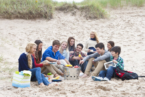 Teenage friends enjoying barbecue on beach - JUIF01257