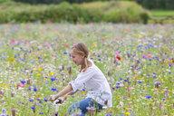 Girl riding bicycle in wildflower field - JUIF01263