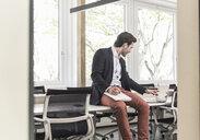 Young businessman sitting in boardroom, preparing for presentation - UUF17692