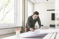 Young architect working on blueprint in bright office - UUF17719