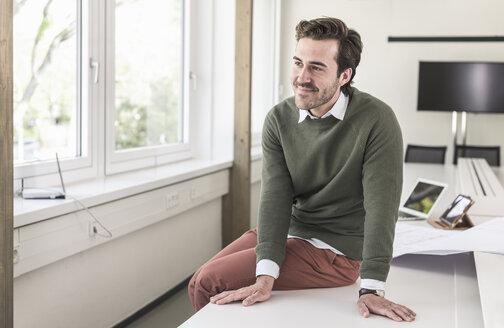 Successful, young businessman sitting in boardroom - UUF17728
