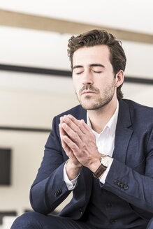 Young businessman praying with eyes closed - UUF17746