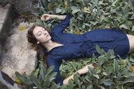Woman sleeping in leafy garden - BLEF06165