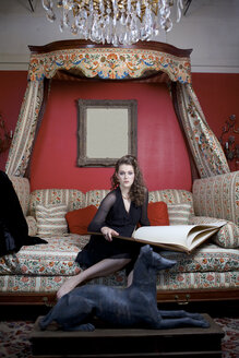 Woman reading oversized book on sofa in ornate living room - BLEF06204