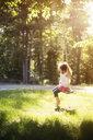 Girl sitting on swing in field - BLEF06360