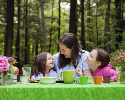 Caucasian mother and daughters sitting at table outdoors - BLEF06432
