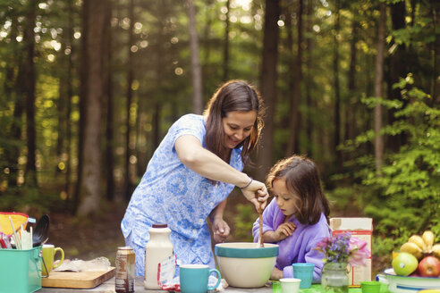 Caucasian mother and daughter cooking in forest - BLEF06441