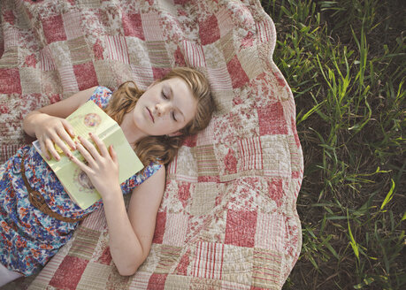 Caucasian girl sleeping with book on blanket - BLEF06465