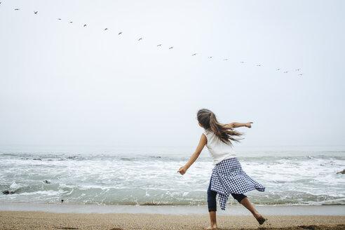 Hispanic girl playing on beach - BLEF06483