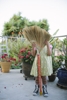 Girl hiding face on patio with broom - BLEF06486