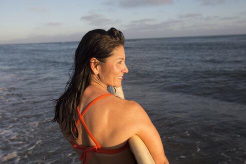 Hispanic woman holding surfboard in ocean - BLEF06516