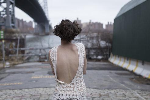 Woman in low-back dress walking in industrial area - BLEF06519