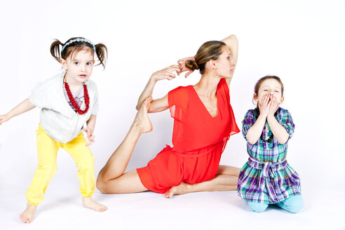 Mother practicing yoga with playful daughters - BLEF06522