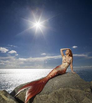 Caucasian mermaid laying on rock near ocean - BLEF06537