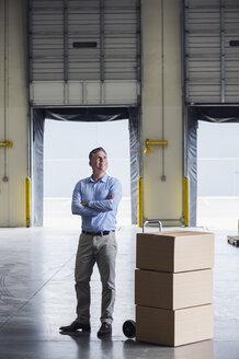 Caucasian businessman standing near cardboard boxes in warehouse - BLEF06579