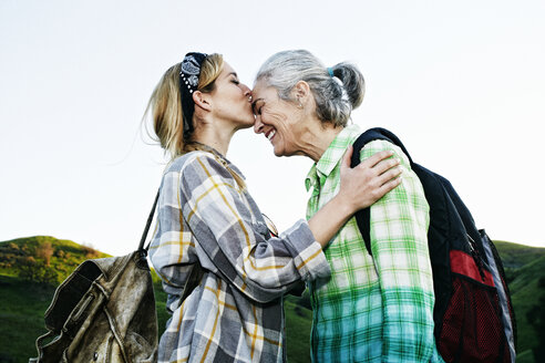 Caucasian daughter kissing mother on rural hilltop - BLEF06597
