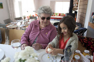 Grandmother and granddaughter cooking at table - BLEF06624