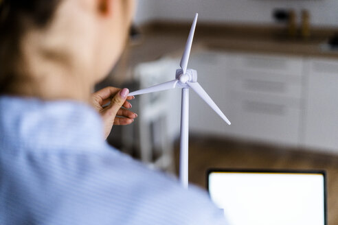 Close-up of woman turning wind turbine modell in office - GIOF06406