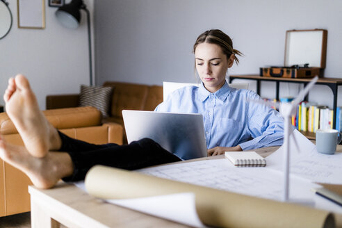 Woman in office working on laptop with feet on table - GIOF06421