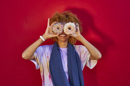 Playful woman holding two donuts in front of her eyes - VEGF00283