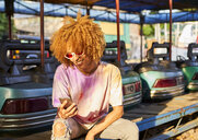 Smiling woman using cell phone at bumper car on a fair - VEGF00289