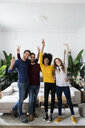 Portrait of four happy friends standing side by side in living room - GIOF06438