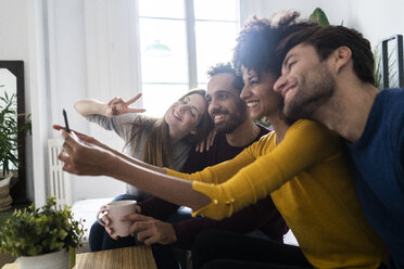 Four happy friends sitting on couch taking a selfie - GIOF06441