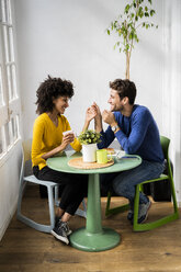 Happy affectionate couple sitting at table at home - GIOF06447