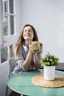 Young woman stting at the window at home with coffee cup and headphones - GIOF06450