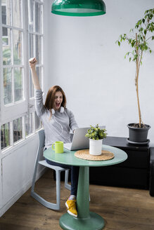 Excited young woman stting at table at home with laptop - GIOF06453