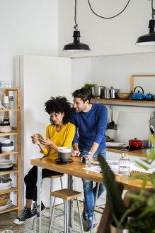 Couple in kitchen at home sharing cell phone - GIOF06459