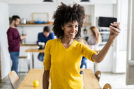 Happy woman taking a selfie at home with friends in background - GIOF06468