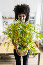 Portrait of smiling woman holding plant at home - GIOF06477