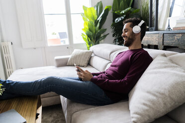 Laughing man sitting on couch with cell phone and headphones - GIOF06480