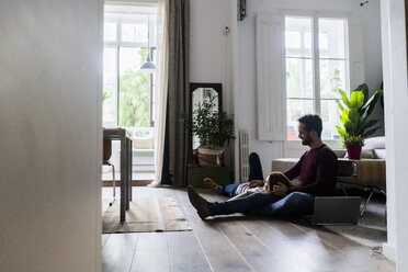 Affectionate couple with laptop relaxing on the floor at home - GIOF06492