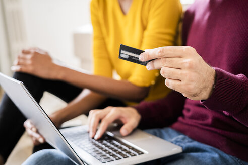 Close-up of couple at home shopping online with laptop and credit card - GIOF06501