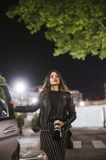 Young woman with camera at a car at night - LJF00111