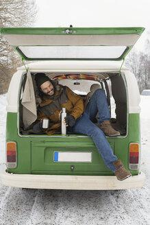 Happy man with electric van in winter landscape having a break, Kuopio, Finland - PSIF00284