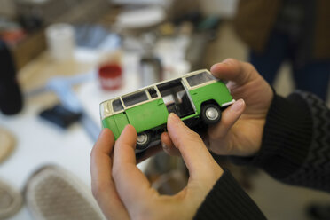 Close-up of woman holding minibus model - PSIF00287