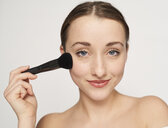 Portrait of smiling young woman with beauty brush - PNEF01538