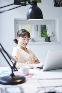 Portrait of laughing young woman working on laptop in an office - PNEF01547