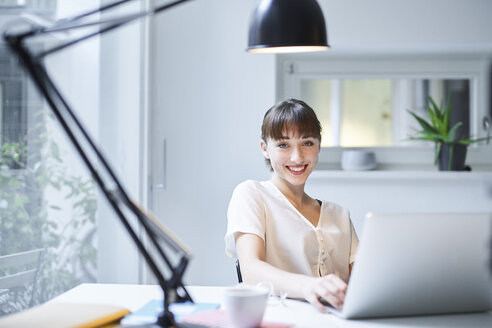Portrait of smiling young woman working on laptop in an office - PNEF01550
