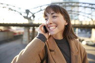 Portrait of happy young businesswoman on the phone outdoors - PNEF01562